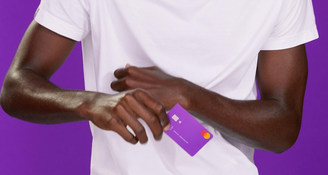 homem de camiseta branca segurando um cartão de crédito Nubank