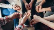 Close-up photo of a small support circle containing five people, focusing on their hands.