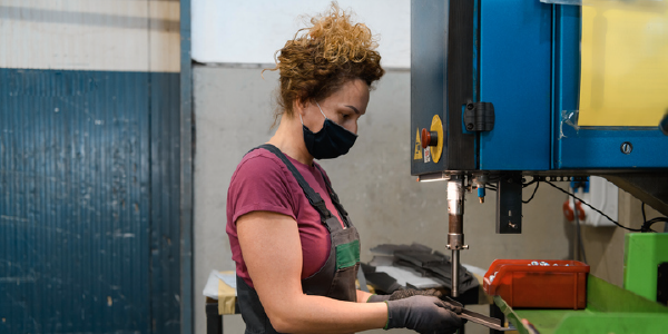 A woman wearing a mask and protective apron works with a metal drill in a workshop.