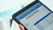 """A person holds a tablet on which the words """"medical billing statement"""" are visible. Below that is a neatly labeled chart."""