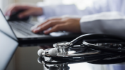 A medical professional uses a laptop. A stethoscope lies on a table in the foreground.