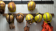 Photo shows eight mining helmets hanging on a wall along with protective gloves and a reflective safety vest.