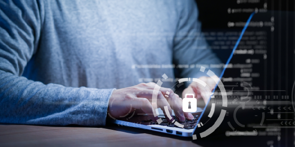 Cybersecurity concept. Photo shows a close-up shot of a man's hands typing on a laptop. Computer code and a lock icon appear in the foreground.