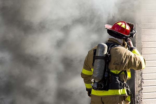 firefighter with a radio in front of a smoky building